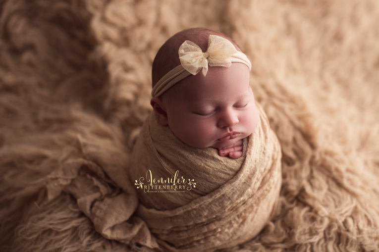 newborn infant posed in the potato sack pose nestled on a tan flokati rug