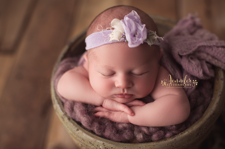 newborn infant posed in bucket